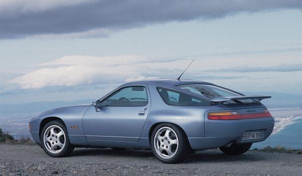 Porsche 928 GTS grise de profil/arrière sous un ciel nuageux