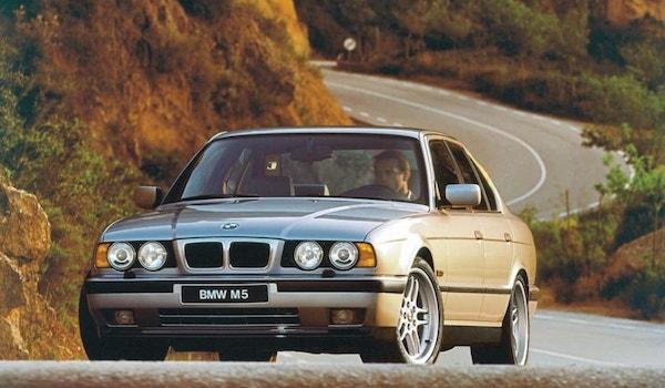 BMW M5 E34 gris clair sur une route sinueuse