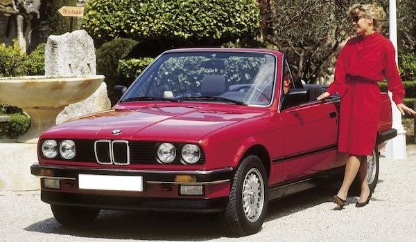 BMW E30 cabriolet rouge décapotable dans un jardin