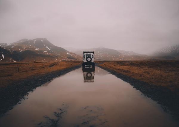 Land Rover Defender blanc sur une route inondée