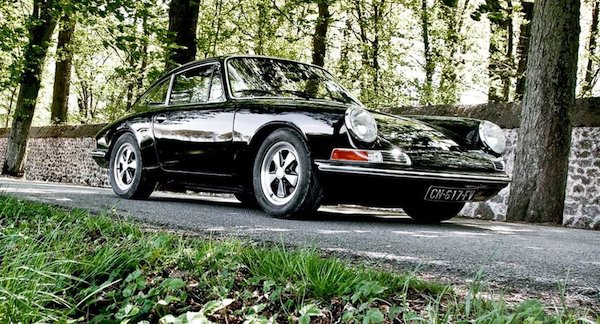 Porsche 912 noire sur une route boisée