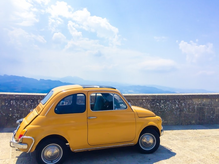 Fiat 500 Classique jaune devant un paysage méditerranéen