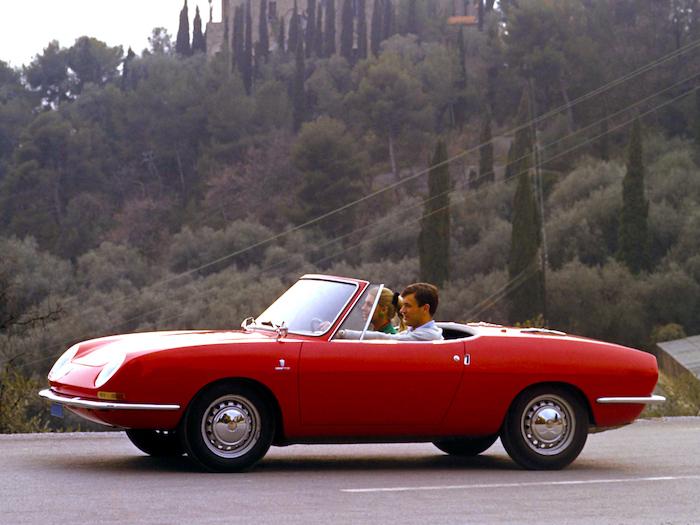 Fiat 850 Spider rouge avec un jeune couple à son bord sur une route italienne