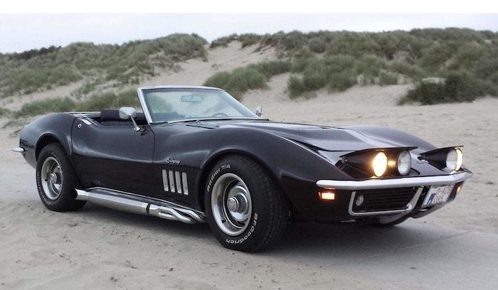 Corvette C3 cabriolet noire de 3/4 face sur une plage au crépuscule