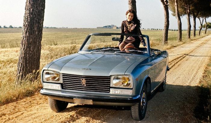 Peugeot 304 S grise de face avec une jeune femme à bord sur un chemin ensoleillé