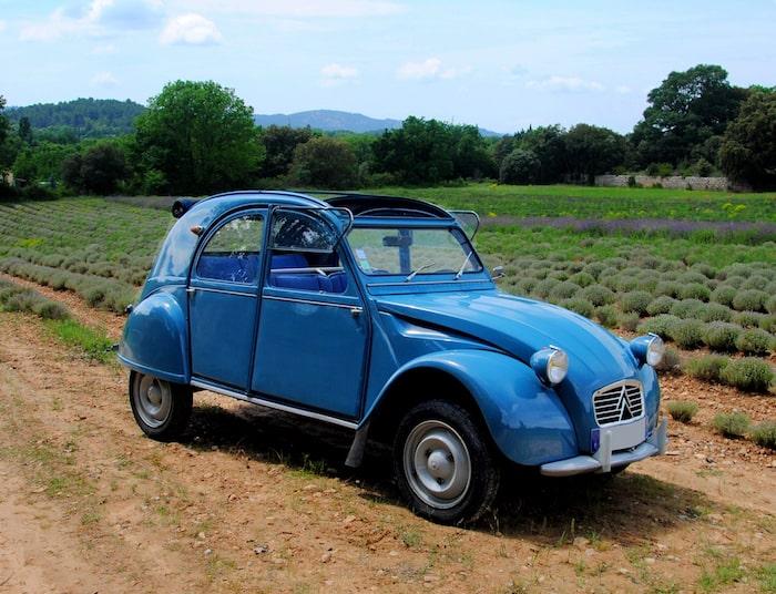 Citroën 2CV bleue de 3/4 face dans un champ