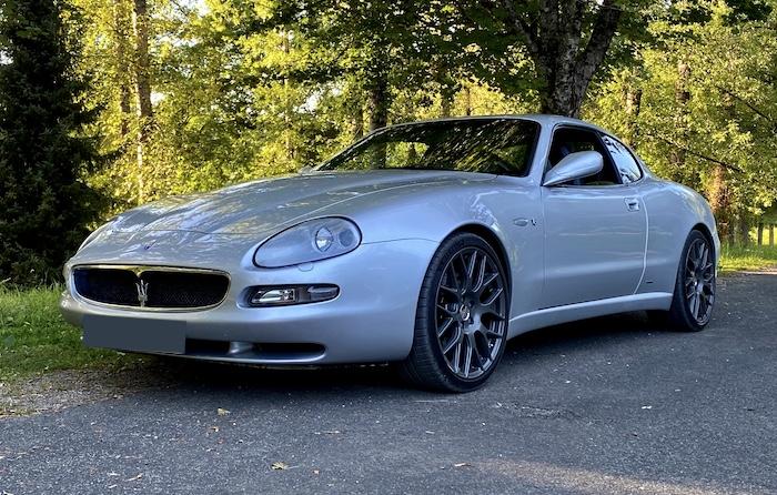 Maserati Coupé Cambiocorsa argenté de 3/4 face devant un bois