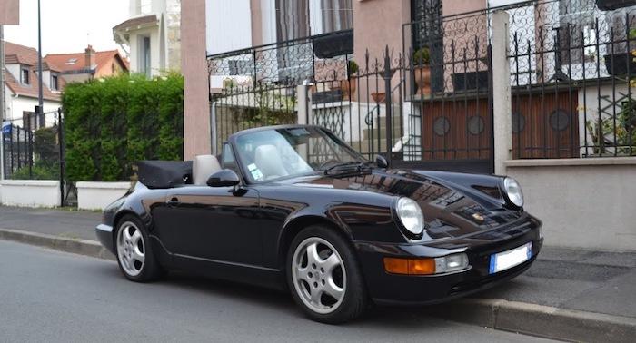 Porsche 964 cabriolet noire de 3/4 face sur un trottoir