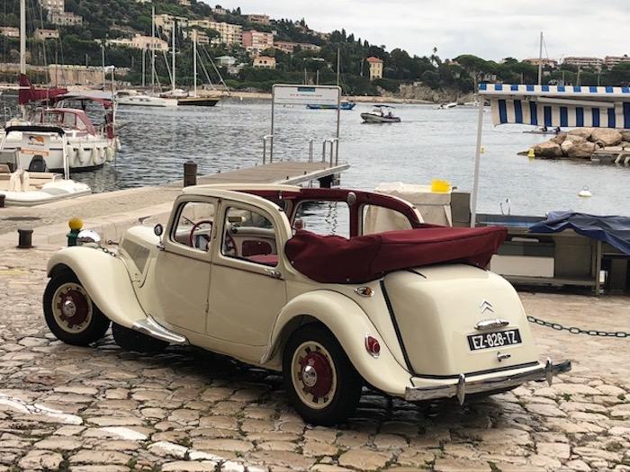 Citroën Traction découvrable beige avec intérieur rouge sur un port méditerranéen
