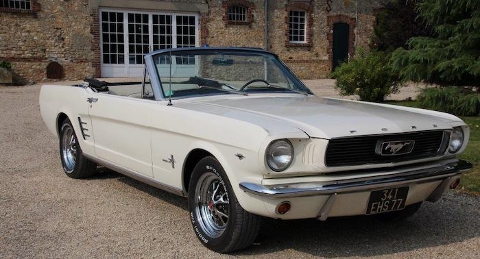 Ford Mustang de 1966 blanche devant une maison de campagne