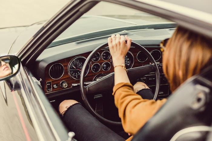 Jeune femme au volant d'une voiture de collection
