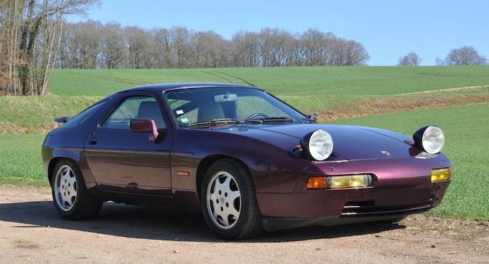 Porsche 928 violette de 3/4 face devant un champ