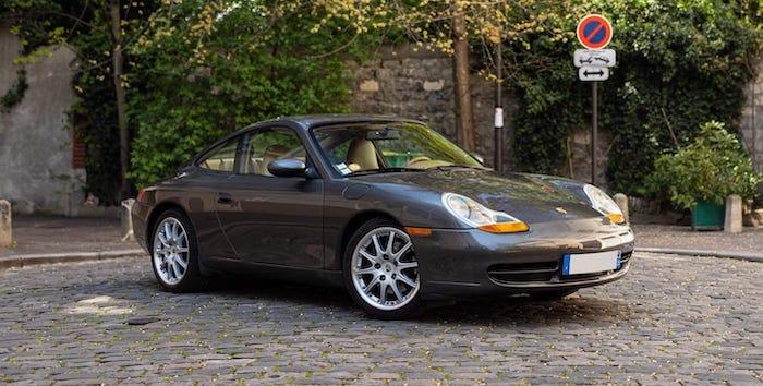 Porsche 911 996 de 2000 grise intérieur havane sur des pavés