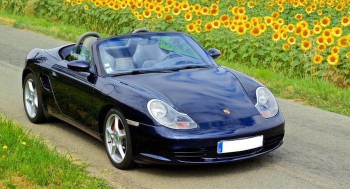 Porsche Boxster 986 bleu marine décapoté sur une route champêtre