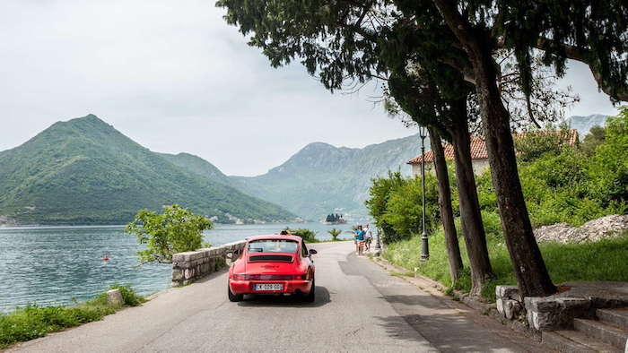 Porsche 964 Carrera 4 rouge longeant un lac