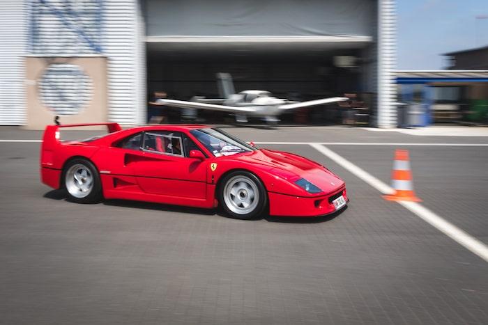 Ferrari F40 rouge en mouvement devant un hangar d'aviation