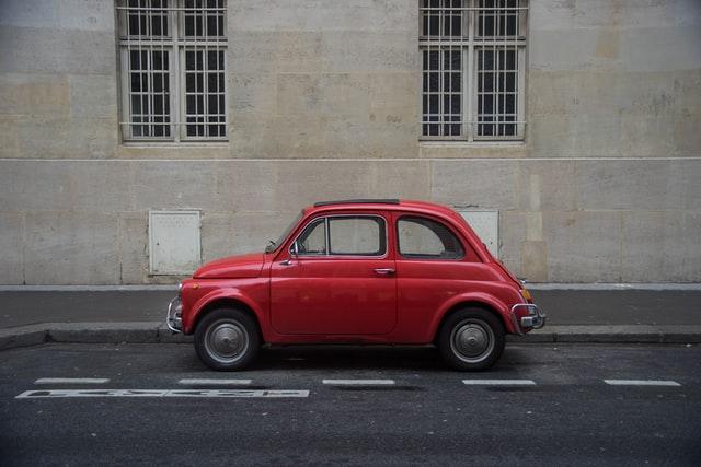 Fiat 500 classique rouge garée dans une rue parisienne