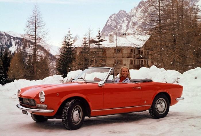 Fiat 124 spyder de profile dans la neige et sa conductrice