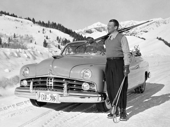 Homme tenant des skis devant un cabriolet Lincoln des années 50 de 3/4 face en montagne