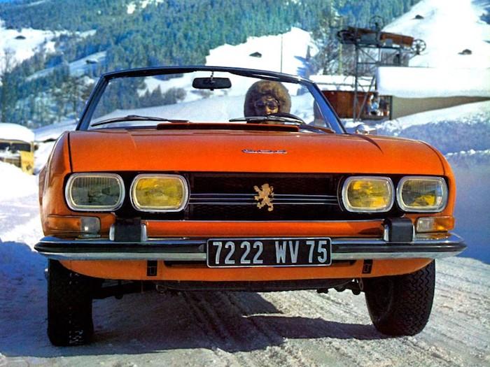 Peugeot 504 cabriolet orange de face en montagne dans la neige