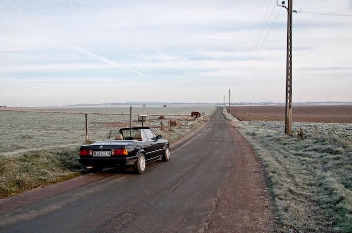 BMW E30 cabriolet sur une route de campagne de 3/4 arrière