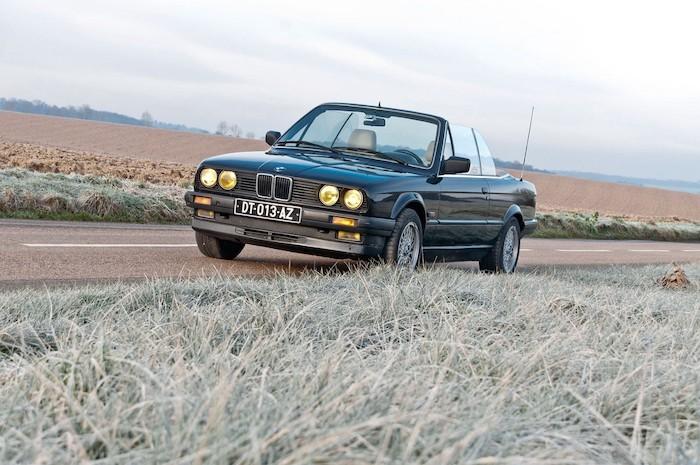 BMW E30 cabriolet de 3/4 face sur une route de campagne